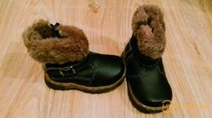 საბავშვო ბაღში აღმზრდელი ეხმარება ბიჭუნას ფეხსაცმლის ჩაცმაში...