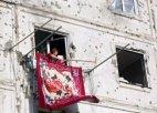 ომიდან ერთ კვირაში ცხინვალში, თავის განადგურებულ სახლში დაბრუნებული ქალი  ხალიჩას ჰფენს აივნიდან