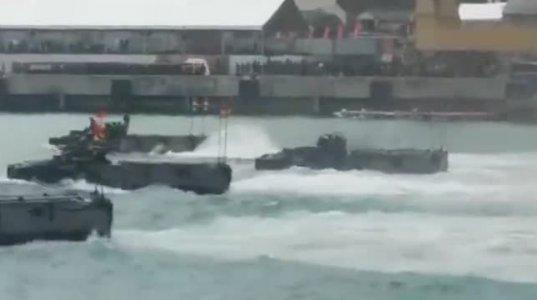 სამხედრო მძიმე ტექნიკა მაღალი სანაპიროდან ხტება წყალში და მიცურავს