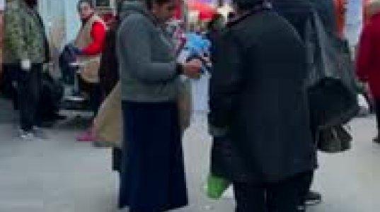 ბოშა ქალი ქუჩაში დგას და პირბადეებს ყიდის კანონდარღვევით. საქართველო